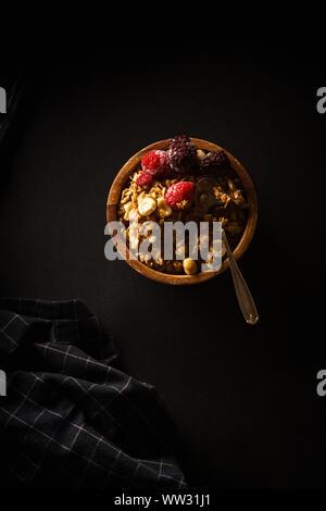 Müsli mit Himbeeren und Brombeeren in Houten mit einer Tasse Kaffee auf Schwarz. - Stockfoto