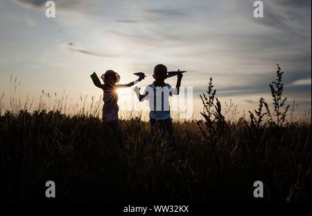 Geschwister spielen im Freien auf einer Wiese bei Sonnenuntergang im Sommer