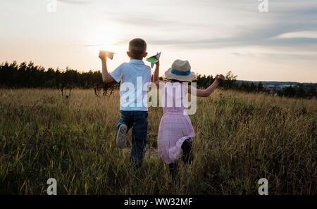 Geschwister, die durch eine Wiese spielen bei Sonnenuntergang im Sommer