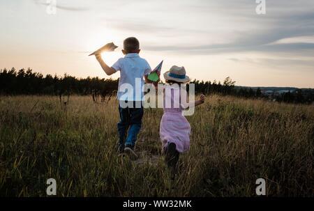 Geschwister, die durch eine Wiese zusammen bei Sonnenuntergang spielen