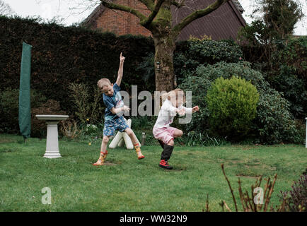 Mädchen und Jungen tanzen draußen im Regen zusammen Stockfoto