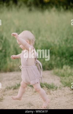 Baby Mädchen läuft in einem Feld - Stockfoto