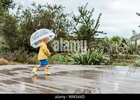 Preschooler Holding einen Regenschirm in Pfützen planschen - Stockfoto