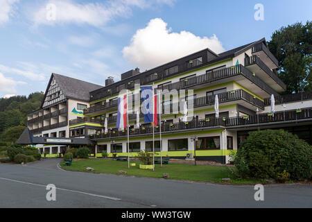 Das Alpin Hotel im Wellness und Ski Village von Grafschaft im Sauerland in der Nähe von Winterberg vor einem blauen Himmel mit Wolken - Stockfoto