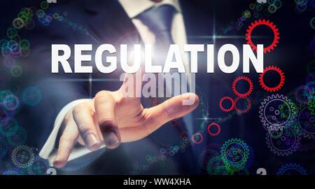 Ein Geschäftsmann Drücken einer Verordnung Business Konzept, das auf einer grafischen Darstellung der Zahnräder - Stockfoto