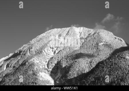 Dahintreibenden Wolken über einem schneebedeckten Berg in Oberbayern, - Stockfoto