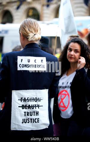 """London, Großbritannien. 13 Sep, 2019. Aussterben Rebellion Aktivisten in weißen Kleidern und 'blutenden Herzen' selbst bis zum Haupteingang der London Fashion Week Messe geklebt. Andere Mitglieder des Aussterbens Rebellion gegossen Eimer von gefälschten Blut um den Eingang und führte eine 'die-in"""", fordert, dass die Modeindustrie die Wahrheit über seinen Beitrag zum Klima- und ökologische Krise Kredit zu sagen: Gareth Morris/Alamy leben Nachrichten - Stockfoto"""
