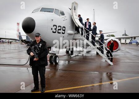 Bewaffnete Polizisten patrouillieren die Show, als VIP-Party besuchen Sie ein Flugzeug der US Navy. Regen, niedrige Wolkenuntergrenze und starke Winde alle aber stoppt die Flugvorführungen auf Frida - Stockfoto
