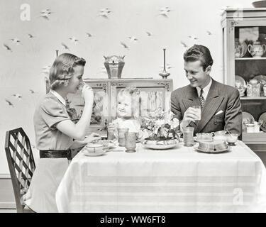 1930er Jahre 1940er Jahre junges Paar, MANN UND FRAU TRINKT ORANGENSAFT lächelnd eine niedliche blonde Tochter am Frühstückstisch - d95 HAR 001 HARS FRÜHSTÜCK MAMA ZUHAUSE GESICHTER NOSTALGISCHE PAAR SCHÖNHEIT SUBURBAN STÄDTISCHE MÜTTER AUSDRUCK ALTE ZEIT NOSTALGIE OLD FASHION 1 JUVENILE CUTE FACIAL KOMMUNIKATION BLONDE JUNGE ERWACHSENE BALANCE TEAMARBEIT starke Freude, Freude LIFESTYLE ZUFRIEDENHEIT FRAUEN VERHEIRATET EHEPARTNER EHEMÄNNER GESUNDHEIT LEBEN ZU HAUSE KOPIEREN RAUM MIT HALBER LÄNGE DAMEN FITNESS TÖCHTER PERSONEN INSPIRATION FÜRSORGLICHE MÄNNER GELASSENHEIT VERTRAUEN ORANGE AUSDRÜCKE VÄTER B&W MORGEN PARTNER ERFOLG WEITWINKEL - Stockfoto