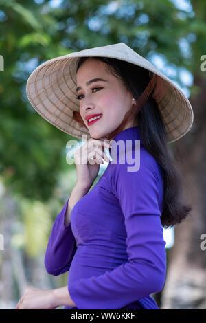 Porträt einer schönen Frau das Tragen einer Tracht und konischen Hut, Vietnam - Stockfoto