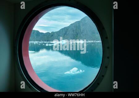 Kleine Eisberge und felsigen Klippen durch ein Kreuzfahrtschiff bullauge Fenster im Fjord von Bredefjord in Narsaq, Kujalleq, Grönland gesehen - Stockfoto