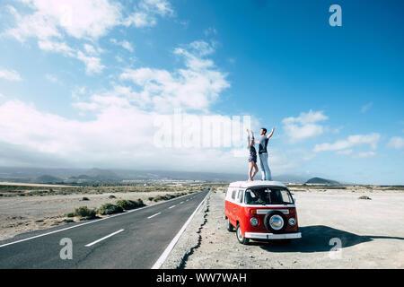 Hippie style für einen alternativen Urlaub Outdoor Freizeit für junge Paare kaukasischen schönen Aufenthalt auf dem Dach eines alten Van in der Nähe von einem langen Weg für Travel Concept. - Stockfoto