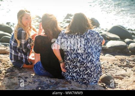 Gruppe der schönen Frau Junge sprechen und lächelnd um in einem Stein Strand auf Teneriffa. team Mädchen Spaß zusammen - Stockfoto