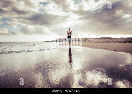 Lonely runner Dame jungen kaukasischen Mädchen am Strand barfuß Stil läuft am Ufer. Wellen und Meer Sport Konzept. Sonnenuntergang und Tag. laufen an der Küste. - Stockfoto