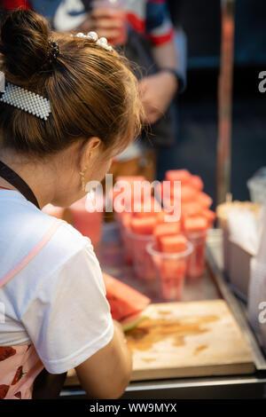 Xian, China - Juli 2019: Frau die Wassermelone in kleine Stücke in Plastikbechern verkauft werden oder Gemischt für Saft in einer im muslimischen Viertel Abschaltdruck - Stockfoto