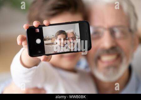 Süße Enkel Umarmung alter Großvater nehmen selfie auf Handy - Stockfoto