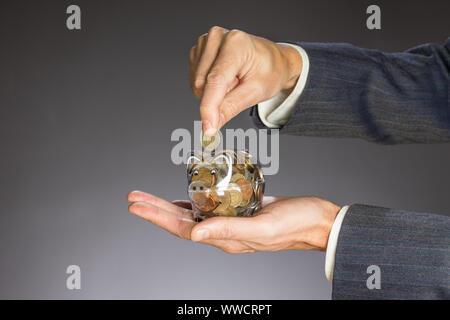 Business Mann mit grauen Jacke setzen Euro Münze in den piggi Bank. European Finance Währung. Guy Geldhaltung box - Stockfoto