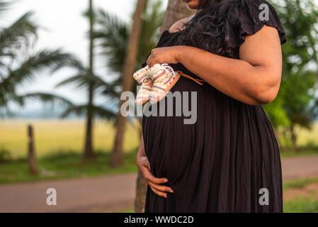 Schwangere Frau im schwarzen Kleid Holding baby Stiefel und zeigt ihren Babybauch an einer im Schießen - Stockfoto