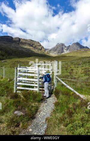 Hillwalker durch küssen Tor in Reh Zaun auf dem Weg zur Blaven in der Black Cuillin Berge auf der Isle Of Skye, Schottland, UK - Stockfoto