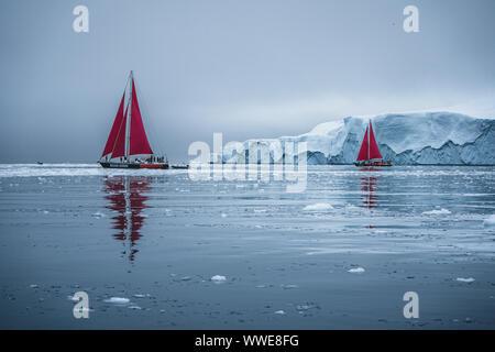 Schöne rote Segelboot in der nächsten zu einem massiven Eisbergs zeigt die Skala Arktis. Kreuzfahrt unter schwimmende Eisberge in der Diskobucht Gletscher