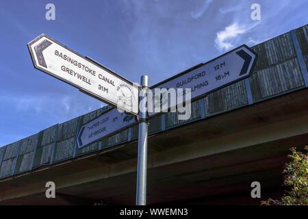 Leinpfad Richtung Wegweiser übersicht Wanderwege und Entfernungen an der Kreuzung des Flusses Wey und Basingstoke Canal in Weybridge, Surrey, Großbritannien - Stockfoto