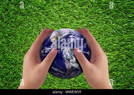 Liebe und Sorgfalt die Erde Konzept, Hand- und Blue Planet auf grünem Gras Hintergrund, Natur und Ökologie, Elemente dieses Bild eingerichtet, die von der NASA - Stockfoto