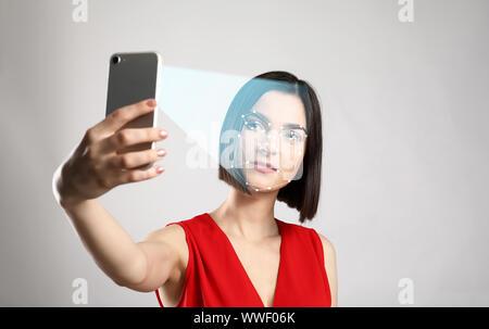 Junge Frau mit Mobiltelefon mit Gesichtserkennung System für den Datenschutz Tel. - Stockfoto
