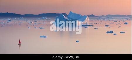 Kleine rote Segelboot Kreuzfahrt unter schwimmende Eisberge in der Diskobucht Gletscher mitternachtssonne Saison von polaren Sommer. Ilulissat, Grönland. Unesco