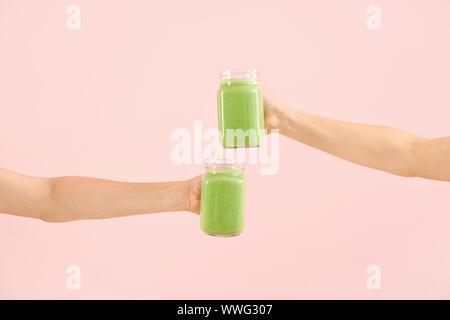 Weibliche Hände mit leckeren grünen Smoothie in Mason Gläser auf farbigen Hintergrund - Stockfoto