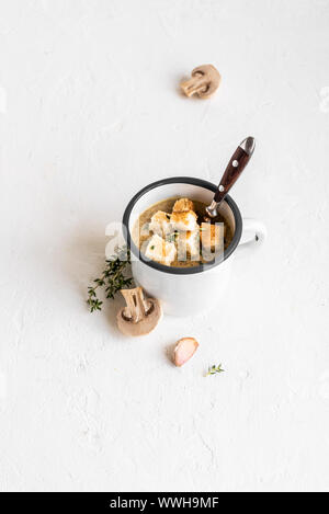 Pilzsuppe. Hausgemachte champignons Creme Suppe mit Croutons in Emaille Tasse. Gesunde und comfort food Konzept, kopieren. - Stockfoto