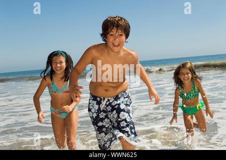 Kinder laufen durch Wellen - Stockfoto