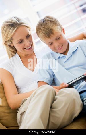 Frau und Junge in Wohnzimmer mit handheld-Spiel smil - Stockfoto