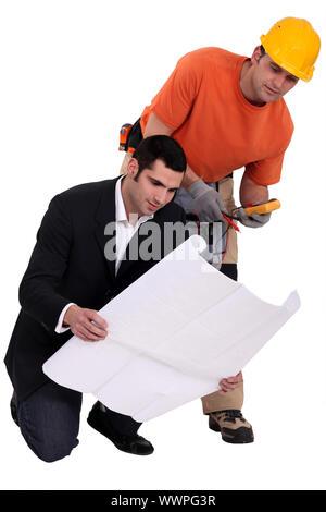 Elektriker und Architekten, die Pläne zu betrachten - Stockfoto