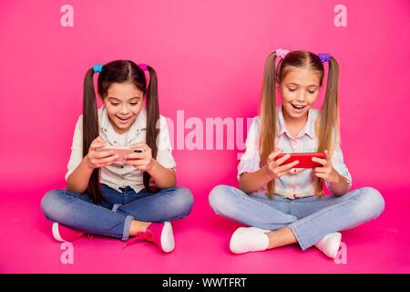 Nahaufnahme Foto zwei Leute wenig Alter sie ihre Mädchen halten Hände arme neue Telefone sitzen Stock süchtig Videospiele lässige Jeans Denim kariert - Stockfoto