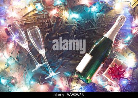 Eine Flasche Champagner, Gläser und einem Geschenkkarton mit einer roten Schleife auf einen schwarzen Stein Hintergrund umgeben - Stockfoto