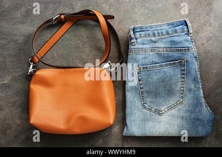 Flach Blau einer Jeans und einem braunen Leder Tasche auf einem dunklen Hintergrund Textur. Weibliche herbst Fashion Outfit. Ansicht von oben - Stockfoto