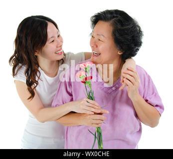 Junge Asiatin Nelke Blume zu ihrer Mutter, auf weißem Hintergrund - Stockfoto