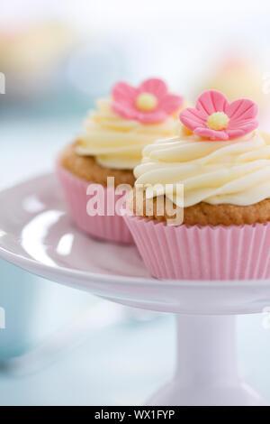 Rosa Blume Cupcakes auf einem Kuchen stand - Stockfoto