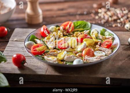 Frische hausgemachte Salate mit natürlichen Zutaten - organische sauber Gemüse, Hähnchen Fleisch und guail Eier, würzigen Senf in einer Platte - Stockfoto