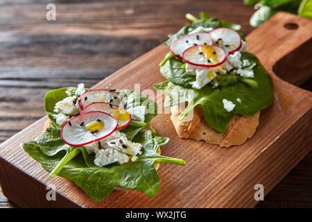 Ciabatta Toast mit Frischkäse, Scheiben von Rettich, frischen Spinat, Leinsamen auf Holz- Hintergrund.