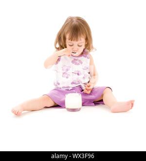 Bild von kleinen Mädchen Essen Joghurt über weiß - Stockfoto