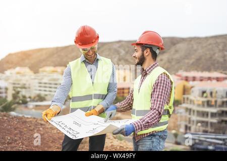 Arbeitnehmer Ingenieure der Diskussion über das neue Gebäude - Junge Baumeister lesen das Projekt in der Baustelle - Stockfoto