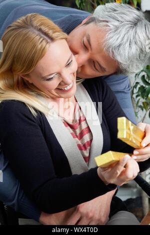 Zärtlich im mittleren Alter Mann, Küssen, Frau, als sie Gegenwart öffnet - Stockfoto