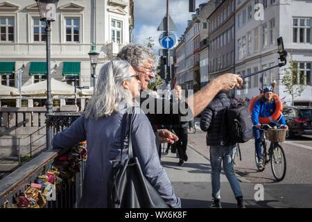 Ein Paar mit einem selfie-Stick ein eigenes Bild auf dem Nyhavnsbroen Brücke zu nehmen, Nyhavn, in Kopenhagen, als Radfahrer mit einem rettungsring Fahrten Vergangenheit - Stockfoto