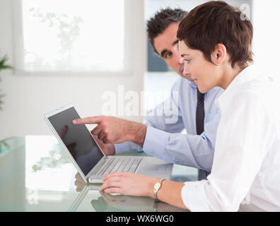 Mann zeigt auf etwas zu seiner Sekretärin auf einem Laptop in einem Büro - Stockfoto