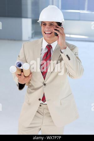 Lächelnd Architekt auf Handy mit Blaupausen - Stockfoto