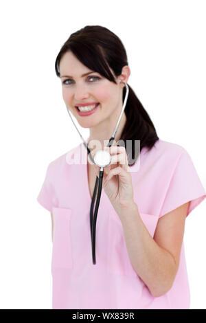 Strahlende Krankenschwester zeigt ein Stethoskop auf einem weißen Hintergrund - Stockfoto
