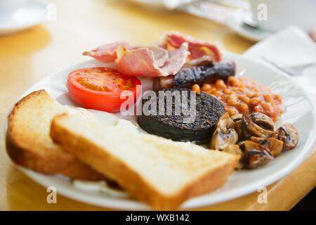 Mit schottischem Frühstück mit Toast, Rührei, Baked Beans, gegrillte Blutwurst, Wurst, Tomaten, Champignons und Speck - Stockfoto