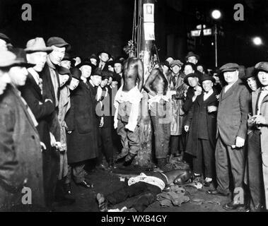 Postkarte des 1920 Duluth, Minnesota Lynchjustiz. Zwei der schwarzen Opfer sind immer noch hängen, während das dritte auf dem Boden ist. Postkarten der Lynchmorde waren beliebte Souvenirs in den USA.