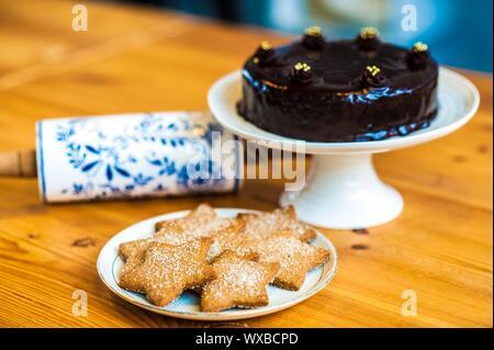Reiche Schokoladenkuchen und Sterne geformt Cookies servierbereit. Nudelholz auf den Tisch. - Stockfoto
